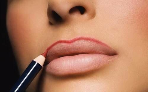 женщина красит губы карандашом