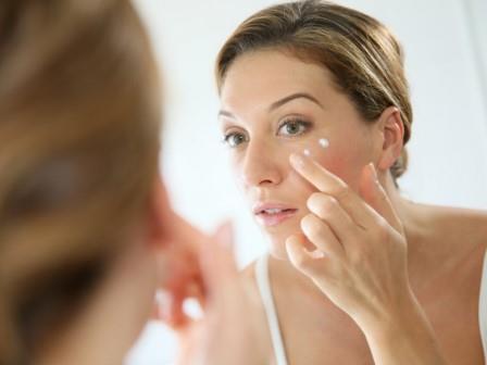 женщина смотрит в зеркало и мажится кремом