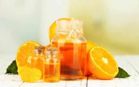 апельсины на столе и бутылочка с апельсиновым маслом