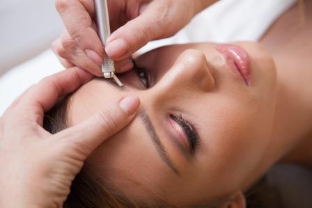 женщине делают перманентный макияж бровей