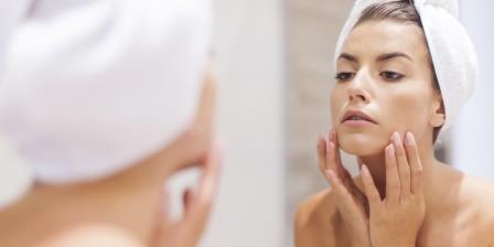 женщина мажется кремом перед зеркалом