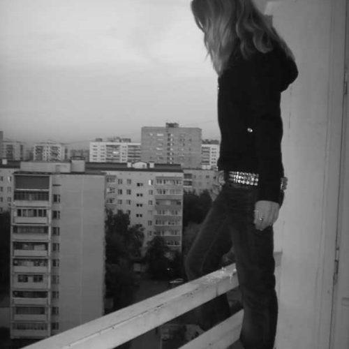 девушка стоит на краю подоконника