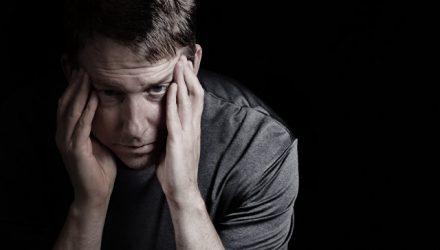 мужчина сидит в темноте и держится за голову