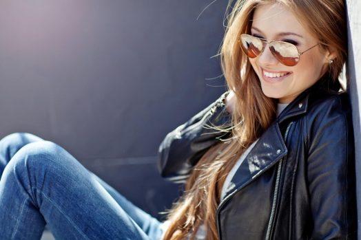 девушка в очках от солнца сидит и улыбается