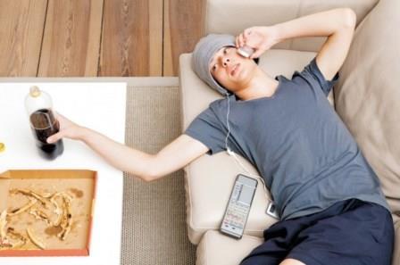 парень лежит на диване и говорит по телефону
