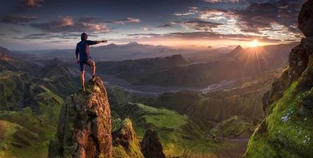 человек стоит на вершине горы и указывает в даль