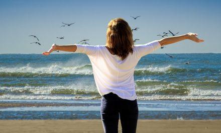 раставив руки девушка смотрит на море