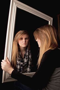 девушка грустная смотрит в зеркало