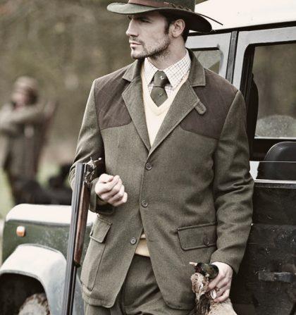 мужчина в пиджаке и с ружьем