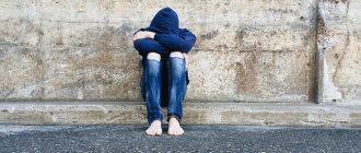 подросток сидит обняв колени