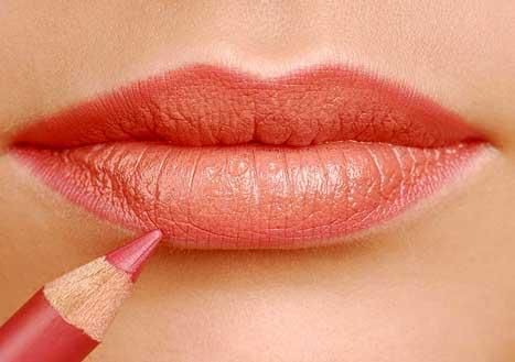 девушка красит губы карандашом