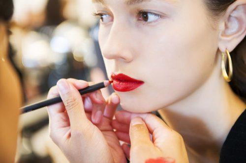 девушке красят губы карандашом