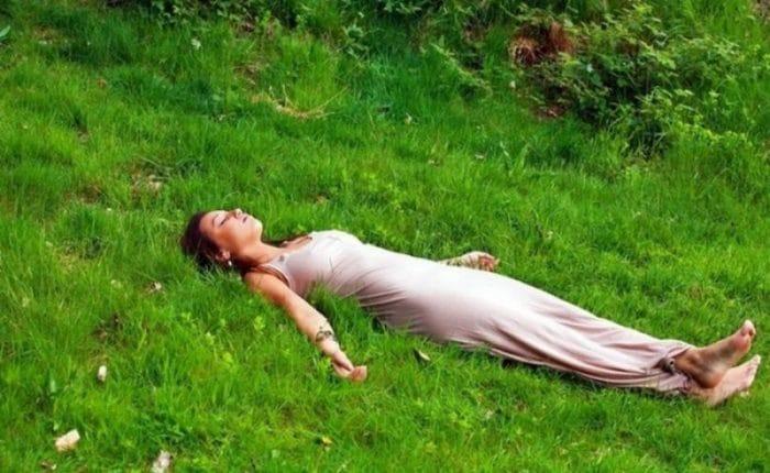 Женщина релаксирует лежа на траве